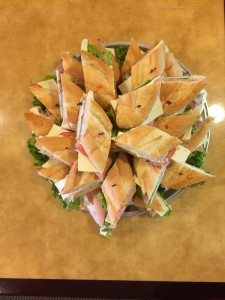 Angle sliced lunchmeat sandwiches on hoagie platter