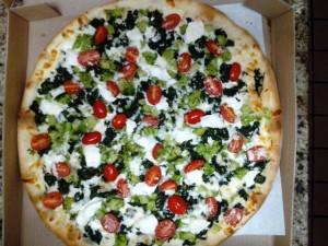 Broccoli and tomato pizza in pizza box