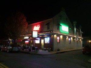 Exterior of Nick's Pizza Restaurant at night with neon lights